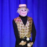 Jongleur steht verkehrt auf der Bühne, ist im Rücken ein alter Mann und jongliert Bälle