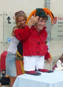 Frowin der Gaukler bei einer Mitmachnummer am Spectaculum zu Friesach. Gemeinsam mit einer Freiwilligen aus dem Puplikum entsteht ein kleiner Mann mit Narrenkappe. Beide lachen.