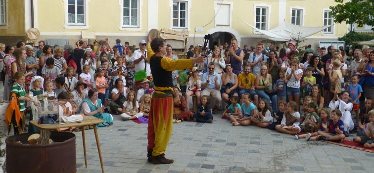 Frowin der Gaukler in roter und gelber Gewandung. Ein großer Publikumskreis schenkt dem mittelalterlichen Narren begeistertes Handgeklapper nach dem Auftritt.