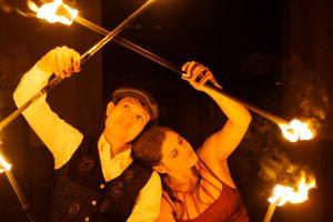 La Nina & Frowin sind Feuerkünstler aus Kärnten. Auf dem Fote sind beide Artisten aneinander gelehnt und bilden mit ihren Feuerstäben ein Muster (Raute). Frowin trägt ein weißes Hemd mit schwarzer Jacke, La Nina ein rotes Kleid.
