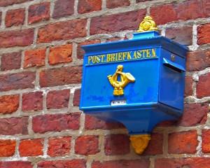 Der blaue Briefkasten an der Ziegelwand dient als Sinnbild für die Kontaktseite von Frowin dem Gaukler.